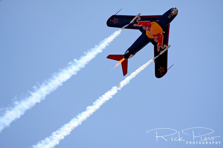 """Bill Reesman demonstrates his meticulously maintained Red Bull MiG-17F during an air show at Madera, California, in May of 2009. Reesman's MiG-17F was built in Poland in 1959 and entered active service in the Polish Air Force as a Cold War warrior, patrolling the Iron Curtain for about 25 years until it was parked in an aircraft """"bone yard"""" in Poland. Reesman had the aircraft rebuilt after his first MiG 17 exploded and caught fire during takeoff."""