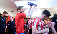 Lincoln City's Josh Vickers, left, pours champagne over team-mate Tom Pett in the changing room as they celebrate winning the league<br /> <br /> Photographer Chris Vaughan/CameraSport<br /> <br /> The EFL Sky Bet League Two - Lincoln City v Tranmere Rovers - Monday 22nd April 2019 - Sincil Bank - Lincoln<br /> <br /> World Copyright © 2019 CameraSport. All rights reserved. 43 Linden Ave. Countesthorpe. Leicester. England. LE8 5PG - Tel: +44 (0) 116 277 4147 - admin@camerasport.com - www.camerasport.com