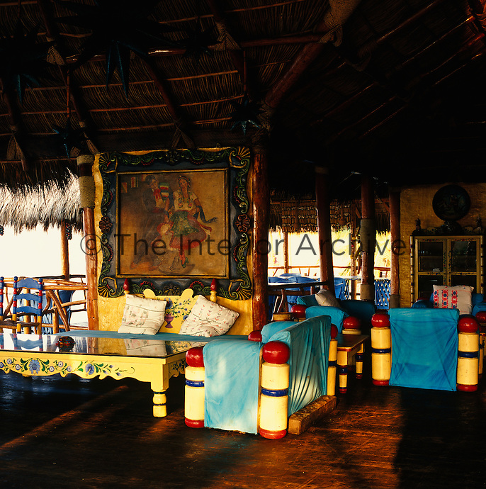 The open-plan hotel lounge is furnished with Mexican hand-painted wooden furniture