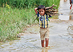 A boy carries firewood through a flooded rice field in the Jamtoli Refugee Camp near Cox's Bazar, Bangladesh. More than 600,000 Rohingya refugees have fled government-sanctioned violence in Myanmar for safety in this and other camps in Bangladesh.