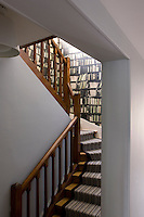 The staircase leading to the upper floor of the apartment is covered with a striped carpet and the walls are hung with a vintage trompe l'oeil design of library shelving