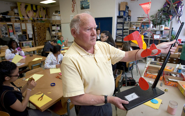 WATERBURY, CT. 02 April 2009-040209SV02--Dr. Ted Martland, former deputy superintendent of schools in Waterbury and mobile artist, show off one of his mobiles to an art class at Kennedy High School in Waterbury. Martland was giving a class on the art of making mobiles to the art class at the School in Waterbury Thursday.<br />  Steven Valenti Republican-American