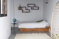 This guest bedroom is furnished with a simple wooden platform bed