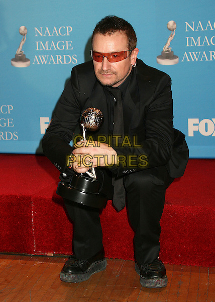 BONO.38th Annual NAACP Image Awards at the Shrine Auditorium - Press Room, Los Angeles, California, USA, .2 March 2007..full length sitting holding trophy award orange sunglasses.CAP/ADM/BP.©Byron Purvis/AdMedia/Capital Pictures.