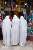 Women in burkas shopping.