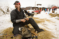 Lance Mackey boots his dogs shortly before leaving Ruby in first place on Friday during Iditarod 2008