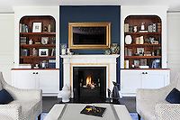 Hand-crafted shelves and cupboards beside the reception room fireplace display books and keep-sakes, while  a gold frame on the chimney breast discreetly belies a modern luxury