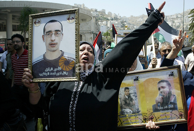 Palestinian women hold pictures of their relatives, held in Israeli jails, during a protest calling for their release in the West Bank city of Nablus, Thursday, July 7, 2011. Israel currently holds about 5,600 Palestinian prisoners in its prisons according to the Israeli prison spokesman. Photo by Wagdi Eshtayah