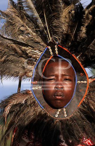 Lolgorian, Kenya. Siria Maasai Manyatta; 'lion head' moran with symbolic feather headdress with beads and cowrie shells.