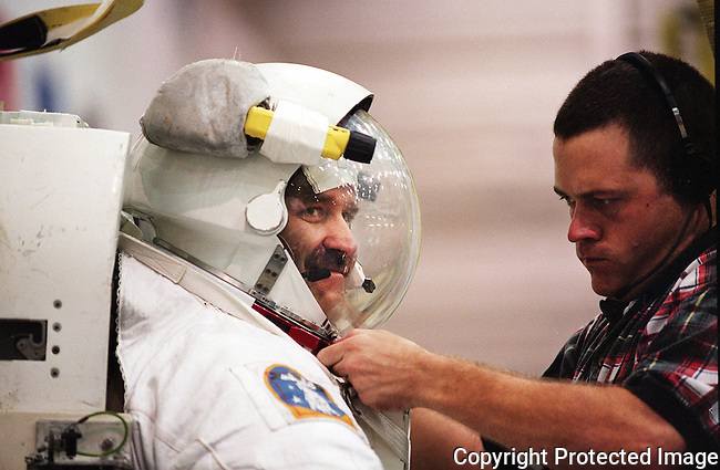 NASA Mission Specialist John Grunsfeld is helped into his spacesuit prior to entering the Neutral Boyancy Laboratory and undergoing a simulation at Johnson Space Center in Houston Texas, Friday, Sept. 10, 1999.(Brian Myrick)