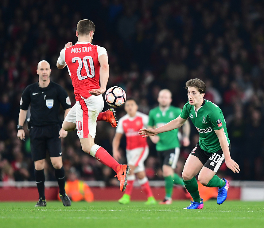 Lincoln City's Alex Woodyard vies for possession with Arsenal's Shkodran Mustafi<br /> <br /> Photographer Chris Vaughan/CameraSport<br /> <br /> The Emirates FA Cup Quarter-Final - Arsenal v Lincoln City - Saturday 11th March 2017 - The Emirates - London<br />  <br /> World Copyright &copy; 2017 CameraSport. All rights reserved. 43 Linden Ave. Countesthorpe. Leicester. England. LE8 5PG - Tel: +44 (0) 116 277 4147 - admin@camerasport.com - www.camerasport.com