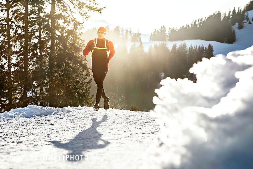 A male runner running on snow at sunset on a cold winter day