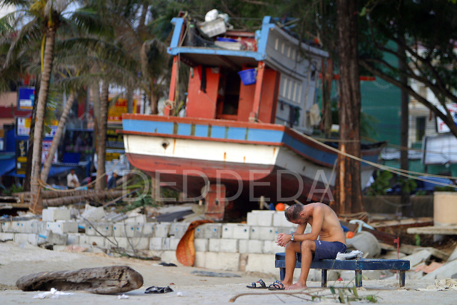 A foreign tourist hangs his head in sorrow as he sits alone on Patong Beach the day after the tsunami destroyed sections of Phuket Island, Thailand. On December 26, 2004, a major earthquake generated tsunamis that ravaged coastlines from Southeast Asia to Africa. Approximately 275,000 people were killed and tens of thousands were left homeless, making it one of the deadliest natural disasters in modern history.