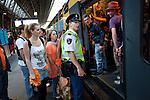 Amsterdam, 30 april 2011.Koninginnedag op en rond Amsterdam Centraal Station; een politieman assisteert bij vertrek van een volle trein..Foto Felix Kalkman