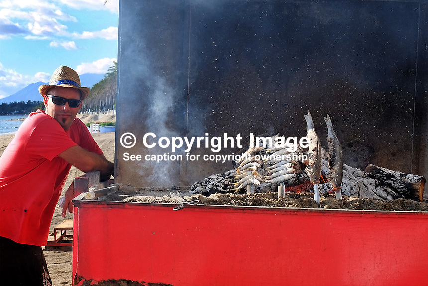 Chef at a chiringuito, open-air beach restaurant, cooking grilled sardines, seabass for clients in Marbella, Malaga, Spain, Espana, 201412150223<br />