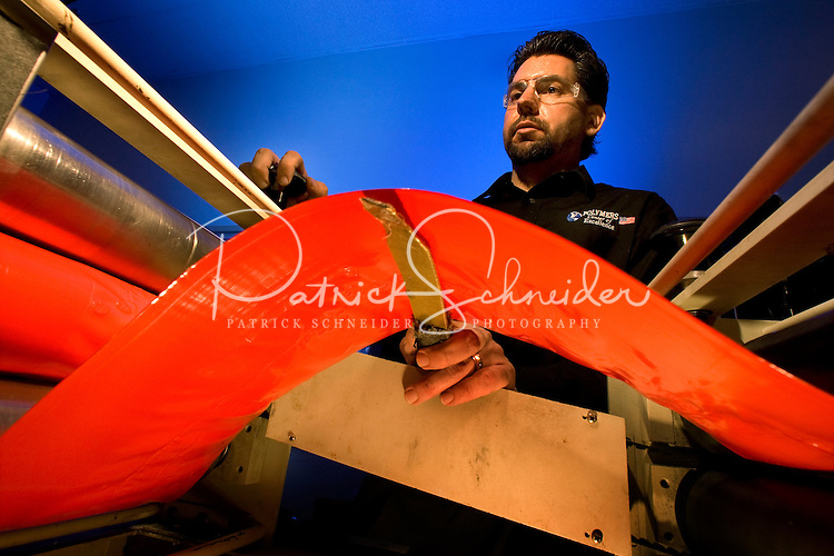 A male worker keeps an eye on a plastic making process at Polymers Center of Excellence in Charlotte. The Polymers Center of Excellence provides state-of-the-art plastics product design, engineering, and analysis services to the medical, transportation, materials handling, packaging, and consumer products industries.