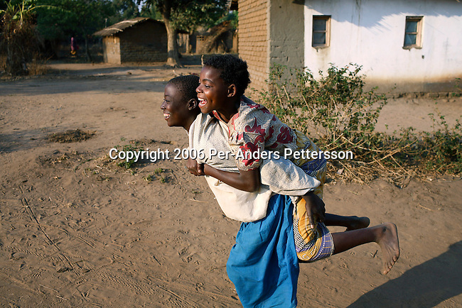 MPHANDULA, MALAWI - AUGUST 18: Mwaiwawo Mphandula age 13, and Ethel Evanse, age 12, play on August 18, 2006 in Mphandula village, about 30 miles outside Lilongwe, Malawi. As a token of friendship they carry each-other. Mphandula is a poor village in Malawi, without electricity or clean water. Nobody owns a car or a mobile phone. Most people live on farming. About 7000 people reside in the village and the chief estimates that there are about five-hundred orphans. Many have been affected by HIV/Aids and many of the children are orphaned. A foundation started by Madonna has decided to build an orphan center in the village through Consol Homes, a Malawi based organization. Raising Malawi is investing about 3 million dollars in the project and Madonna is scheduled to visit the village in October 2006. Malawi is a small landlocked country in Southern Africa without any natural resources. Many people are affected by the Aids epidemic. Malawi is one of the poorest countries in the world and has about 1 million orphaned children. (Photo by Per-Anders Pettersson)