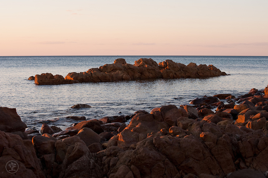 The last of the light hits the rocky shore and tints the sky pink and orange at sunset, Hallet Cove, South Australia.