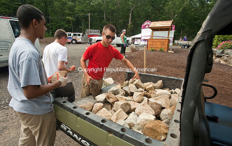 """WOLCOTT, CT-12 AUGUST 2012--081212JS04- Wolcott Lions Club volunteers, from left, Charles Johnson, 17 of Waterbury, Tyler Heavens, 17 of Wolcott and Evan Mitchell, 17 of Wolcott, unload stones as fellow volunteer Tara Centinaro, background, uses the stones to spell out """"Lions"""" as the club prepares for the annual Wolcott Country Fair this upcoming weekend. The fair has moved their fair to the clubs new fairgrounds located at 245 Wolcott Road.  .Jim Shannon Republican-American"""