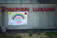 "Switzerland. Canton Ticino. Lugano. The firefighters have hanged a banner on the fire station's walls with the words: ""Everything will be better"" and drawings of a rainbow, smiling sun and clouds, a heart and palms. Due to the spread of the coronavirus (also called Covid-19), the Federal Council has categorised the situation in the country as ""extraordinary"". It has issued a recommendation to all citizens to stay at home, especially the sick and the elderly. The Federal Council (German: Bundesrat, French: Conseil fédéral, Italian: Consiglio federale, Romansh: Cussegl federal) is the seven-member executive council that constitutes the federal government of the Swiss Confederation. From March 16 the government ramped up its response to the widening pandemic, ordering the closure of bars, restaurants, sports facilities and cultural spaces. Only businesses providing essential goods to the population – such as grocery stores, bakeries and pharmacies – are to remain open. 18.03.2020 © 2020 Didier Ruef"