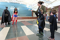 NWA Democrat-Gazette/DAVID GOTTSCHALK Cedar Spearman (from left), 4, hides with his brother Zeal, 5, behind their mother Rachel Thursday, March 21, 2019, in attempt to avoid costumed super heroes Wonder Woman and Batman during Superhero Day at the Jones Center in Springdale. The Jones Center has held a variety of different activities daily during Spring Break. Friday will feature the princesses from the animated film Frozen during Frozen Friday on the ice skating rink at the center.
