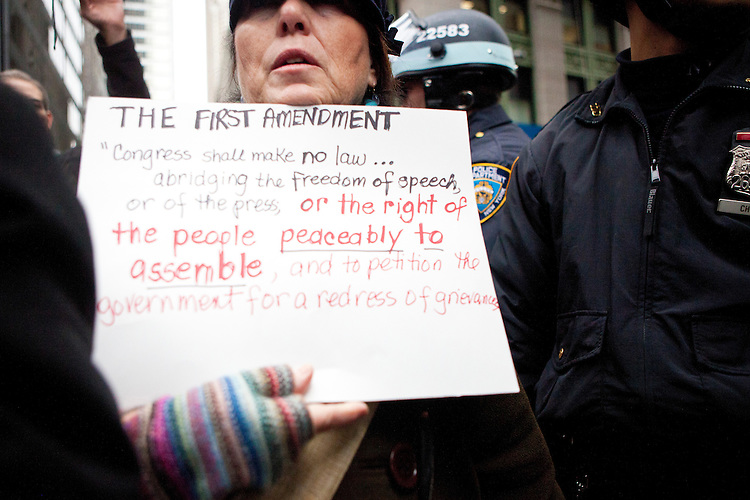 """Police presence is heavy as hundreds of protesters march early in the morning on November 17, 2011 in New York City with the aim to shut down Wall Street and the Stock Exchange.  The action was the first in a day of protests celebrating the two month anniversary of the """"Occupy Wall Street"""" movement.  While many workers were inconvenienced by the human (and police) barricades, the Stock Exchange opened on schedule."""