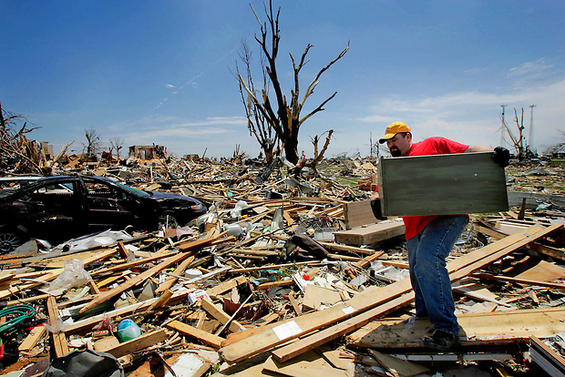 Travis Williamson salvages a piece of furniture from his destroyed house Monday, May 26, 2008 in Parkersburg, Iowa.  An EF5 tornado wiped out the southern third of Parkersburg the evening before, claiming the lives of six people in Parkersburg and two in nearby New Hartford.
