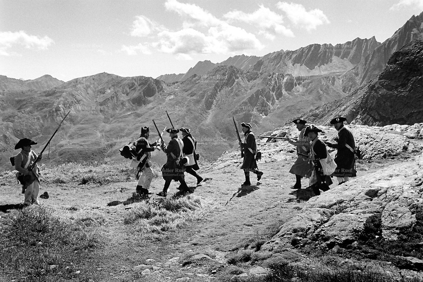 """Italy. Aosta valley. On the border with Switzerland. The Great St. Bernard Pass. A group of men (L)  from the """" Voltigeurs du 3eme régiment suisse"""", all dressed with historic traditional soldiers outfits with muskets during a historical reenactment based on the crossing of the Great St. Bernard Pass on May 13, 1800 by Napoleon Bonaparte and his army (R) on their way to attack the Austrian army in Italy. A musket is a muzzle-loaded, smoothbore long gun, fired from the shoulder. Muskets were designed for use by infantry. A soldier armed with a musket had the designation musketman or musketeer. Great St. Bernard Pass (French: Col du Grand St-Bernard, Italian: Colle del Gran San Bernardo, German: Grosser Sankt Bernhard; 2,469 m (8,100 ft)) is the third highest road pass in Switzerland. Great St. Bernard is one of the most ancient pass through the Western Alps. 12.08.2017 © 2017 Didier Ruef"""