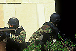 Police officers in gear with guns stalking the outside of a school building to protect the children entering the building.