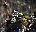 Seattle Seahawks defensive tackle Tony McDonald (99) holds a recovered fumble aloft after defensive Michael Bennett (72) c<br /> stripped the ball from Carolina Panthers running back Jonathan Stewart  in the NFC Western Division Playoffs at CenturyLink Field  on January 10, 2015 in Seattle, Washington. The Seahawks beat the Panthers 31-17. &copy;2015. Jim Bryant Photo. All Rights Reserved.