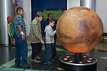 Oakland CA 3rd and 4th grade students on school field trip to Chabot Space and Science Center examine model of planet Mars