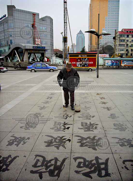 An old man paints Chinese characters on the floor with water outside Dong Chang Lu metro station in the Pudong area of Shanghai.