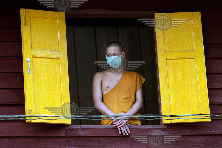 A Buddhist monk looks out over a pile of corpses of people killed in the tsunami which struck South Asia on 26/12/2004. Rescue workers attempted to gather and identify the bodies at various locations, mostly on temple grounds.