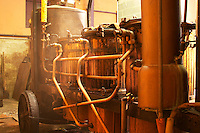Wooden and copper still with steam coming out of the valves. Distillation of marc and fine from wine fermentation residues at M Chapoutier using an old mobile pot still Domaine M Chapoutier, Tain l'Hermitage, Drome Drôme, France Europe