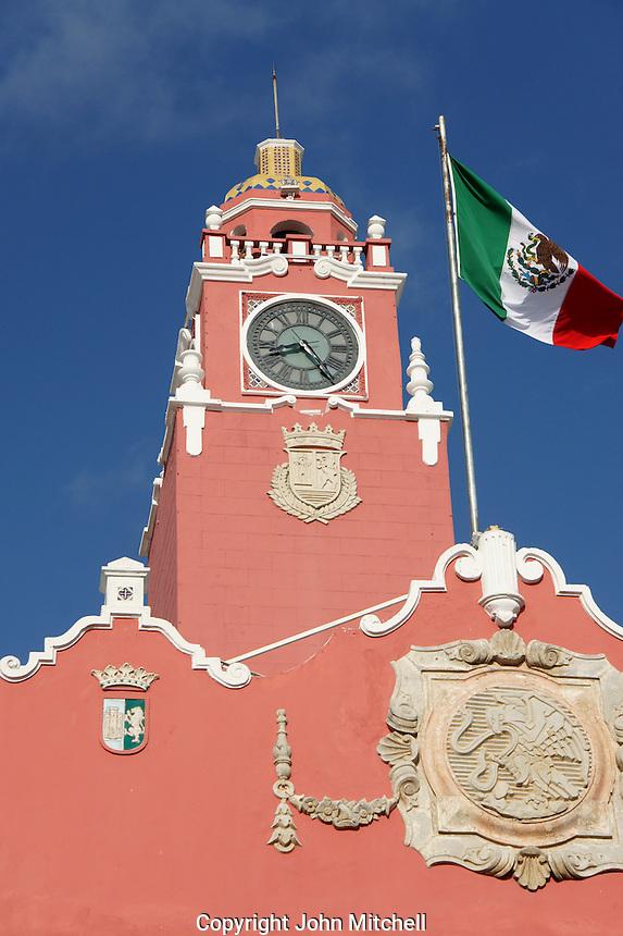 Clock tower of the Municipal Palace or Palacio Municipal and billowing Mexican flag, Merida, Yucatan, Mexico