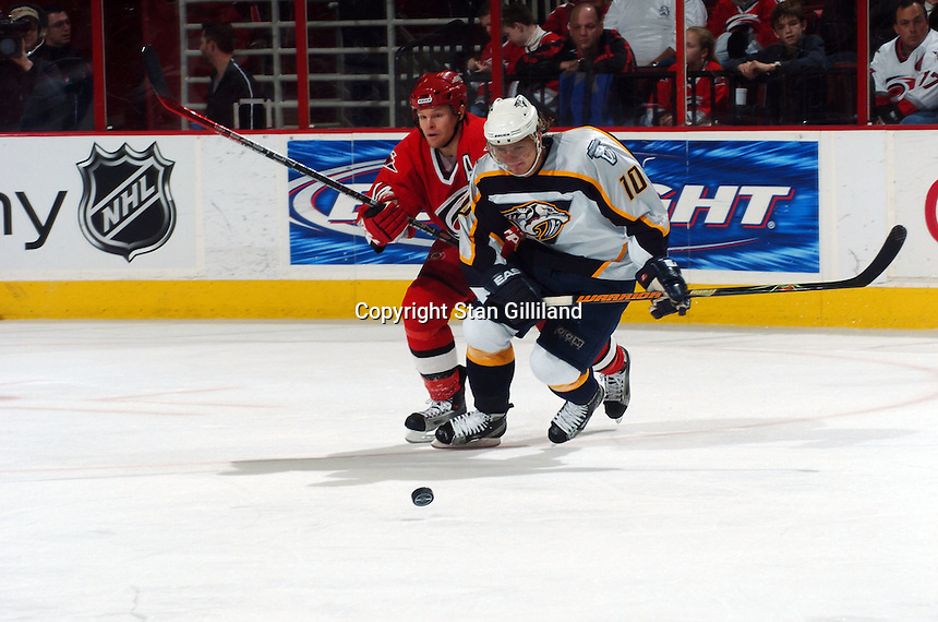 Nashville Predators' Martin Erat (10) of the Czech Republic races Carolina Hurricanes' Kevyn Adams, left, for the puck during their game Friday, January 13, 2006 in Raleigh, NC. Carolina won 5-4 after a shootout.
