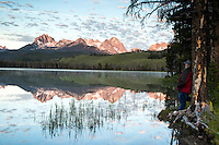 Man taking in the sunrise over the Sawtooth Mountains at Little Redfish Lake in the Sawtooth National Forest.