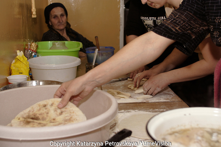 Chechen grandmother with other woman preparing traditional Chechen dish Manty (ravioli with  meat and cheese) for the evening end of the day Ramadan meal, in the kitchen of the URiC Radom Centre..-For security reason, the names of the adult asylum seeker have been change. .-Article 9 of the Act of 13 June 2003 on grating protection on the Polish territory (Journal of Laws, No 128, it. 1176) personal data of refugees are an object of particular protection..-Cases where publication of a picture or name of asylum seeker had dramatic consequences for this persons and is family back in Chechnya. .Please have safety of those people in mind. Thank you.