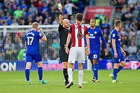 Referee Lee Mason shows a yellow card to Chris Basham of Sheffield United during the Sky Bet Championship match between Cardiff City and Sheffield United at Cardiff City Stadium, Cardiff, Wales on 15 August 2017. Photo by Mark  Hawkins / PRiME Media Images.