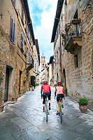 Cyclists riding through the famous Tuscan town of Pienza, Italy