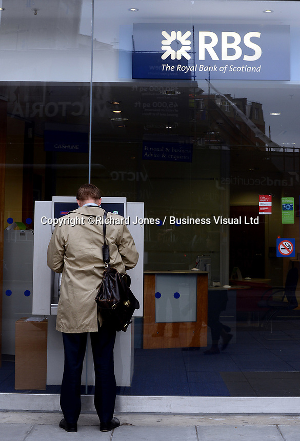 A man uses an RBS ATM in London.  The RBS and other lenders anticipate a surge in lending as the Government helps first time buyers get on the mortgage ladder. 14-Oct-2013