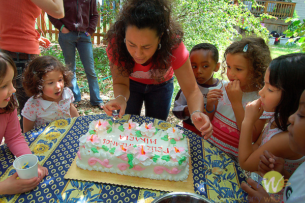 Mikaela's Birthday party. Children and mom lighting birthday cake candles.