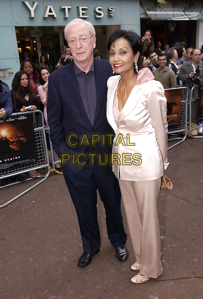 """SIR MICHAEL CAINE & SHAKIRA CAINE.At the European Premiere for """"Batman Begins"""",.Odeon Cinema, Leicester Square, London, .June 12th 2005..full length married husband wife.Ref: FIN.www.capitalpictures.com.sales@capitalpictures.com.©Steve Finn/Capital Pictures."""