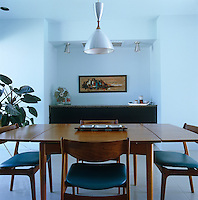 A vintage suite furnishes the dining room and a retro pendant light hangs above the table