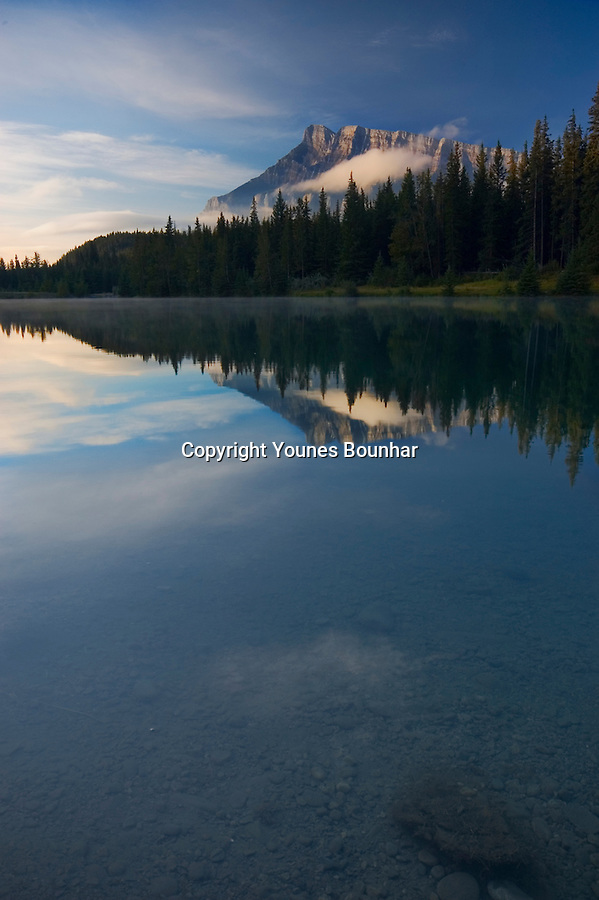 Perfect Reflection of Mount rundle in the early morning. Symmetrical reflection, blue sky and trees, Vertical
