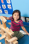 Education preschool 3-4 year olds girl proud of structure she made from wooden building blocks vertical