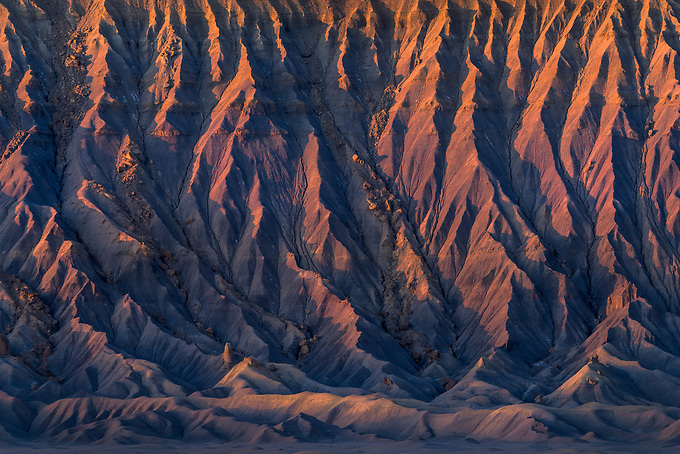 Warm sunrise light filters in from above and illuminates the textures of Factory Butte.