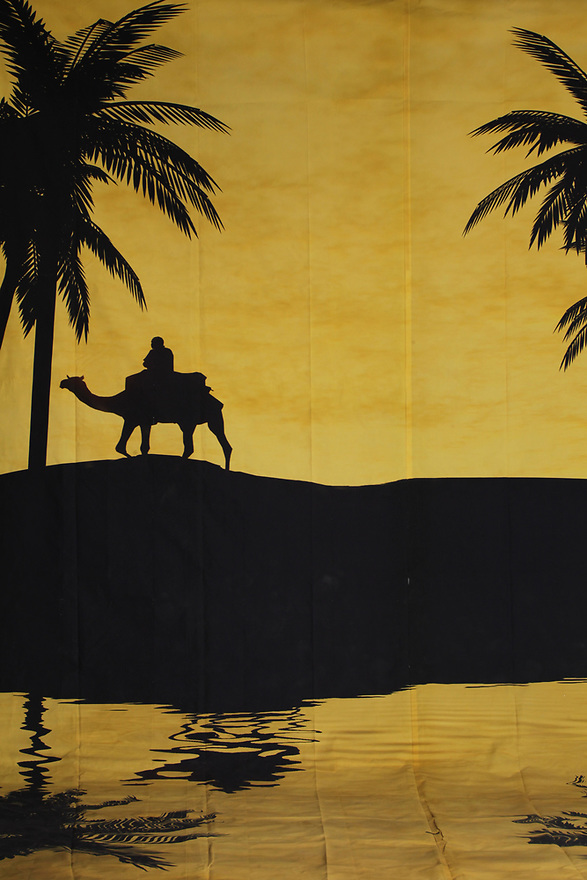 Backdrop featuring a desert scene with camel, sand dunes and palm tree silhouetted against warm sandy tan color