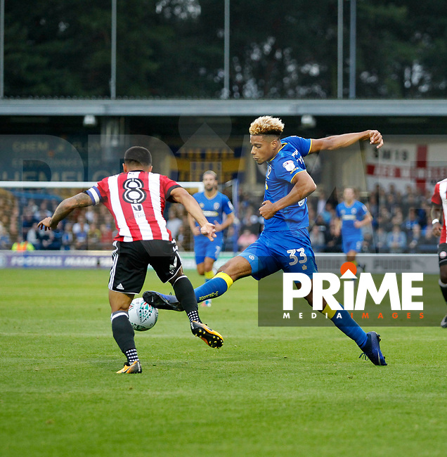 AFC Wimbledon's Lyle Taylor challenges /Brentford's Nico Yennaris for the ball during the Carabao Cup match between AFC Wimbledon and Brentford at the Cherry Red Records Stadium, Kingston, England on 8 August 2017. Photo by Carlton Myrie.