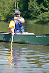 Man in a canoe paddles on the Fox River in Yorkville Illinois USA
